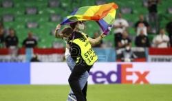 Aktivista na terenu sa zastavom duginih boja tokom intoniranja madjarske himne